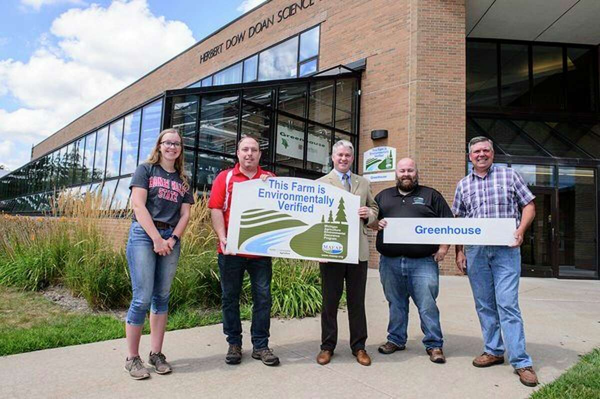 Standing outside SVSU's greenhouse is Abbie Bauer, an SVSU student; Ed Meisel, SVSU greenhouse manager; Andrew Chubb, dean of SVSU's College of Science, Engineering & Technology; Joel Leland, a technician with the Michigan Agriculture Environmental Assurance Program (MAEAP); and Tom Young, a field staff member with MAEAP. (Provided photo/Tim Inman, SVSU)