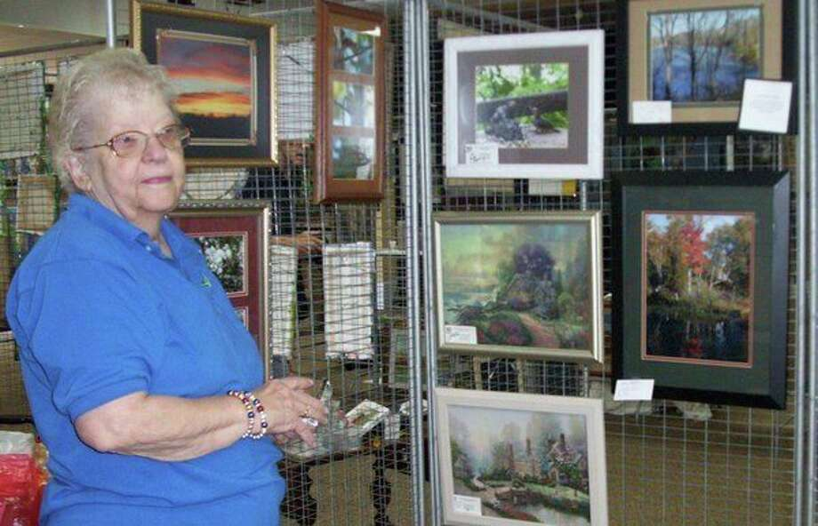 Mary Marcum sets up her booth for the 2018 Gladwin Area Artist Guild Art Show & Sale. Marcum, a Guild member for 20 years, is still active and an officer of the organization. Other charter members are Jeannine Pickard, Ken Marcum, who is still active, John Burt, Mary Lou Reed, Daniel Ogden and Gayle Browne, also active. (Photo provided/ Gladwin Area Artist Guild)