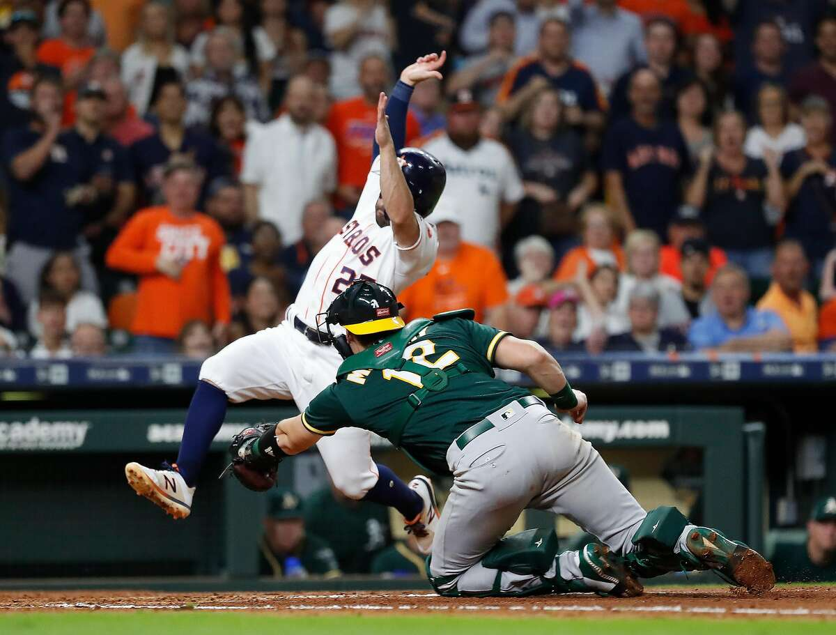 Houston Astros Jose Altuve (27) is tagged out at home by Oakland Athletics catcher Sean Murphy during the fifth inning of a MLB baseball game at Minute Maid Park, Wednesday, Sept. 11, 2019, in Houston.