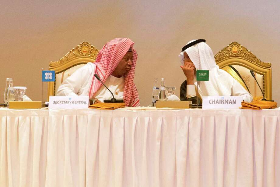 """OPEC Secretary-General Mohammed Barkindo, left, and Saudi Energy Minister Prince Abdulaziz bin Salman, right, confer with each other before an OPEC meeting in Abu Dhabi, United Arab Emirates, Thursday, Sept. 12, 2019. OPEC's Joint Ministerial Monitoring Committee met Thursday in Abu Dhabi as estimates of lowered crude oil demand in 2020 have the cartel considering additional production cuts. Before the meeting started, Prince Abdulaziz again called for """"cohesiveness"""" in OPEC. Photo: Jon Gambrell, AP / Copyright 2019 The Associated Press. All rights reserved."""