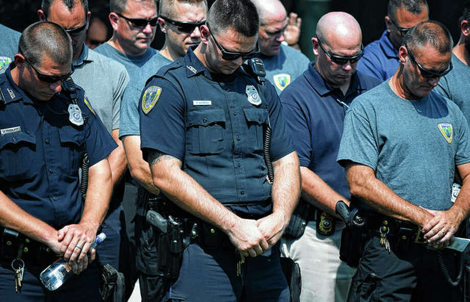 Jacksonville Police Department members bow their heads Wednesday as pastor Jarred Reno of Central Christian Church prays for law enforcement officers during a 9/11 remembrance ceremony. Photo: Samantha McDaniel-Ogletree | Journal-Courier