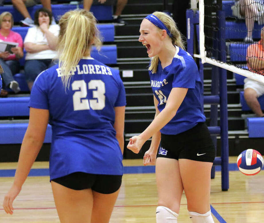 Marquette Catholic's Emma Menke (right) celebrates a her point off a block with Rae Ezell (23) during a Roxana Tourney three-set loss to Jersey last month in Roxana. The teams met again Wednesday night at Marquette, with the Explorers winning in three sets to hand Jersey its first defeat. Photo: Greg Shashack / The Telegraph