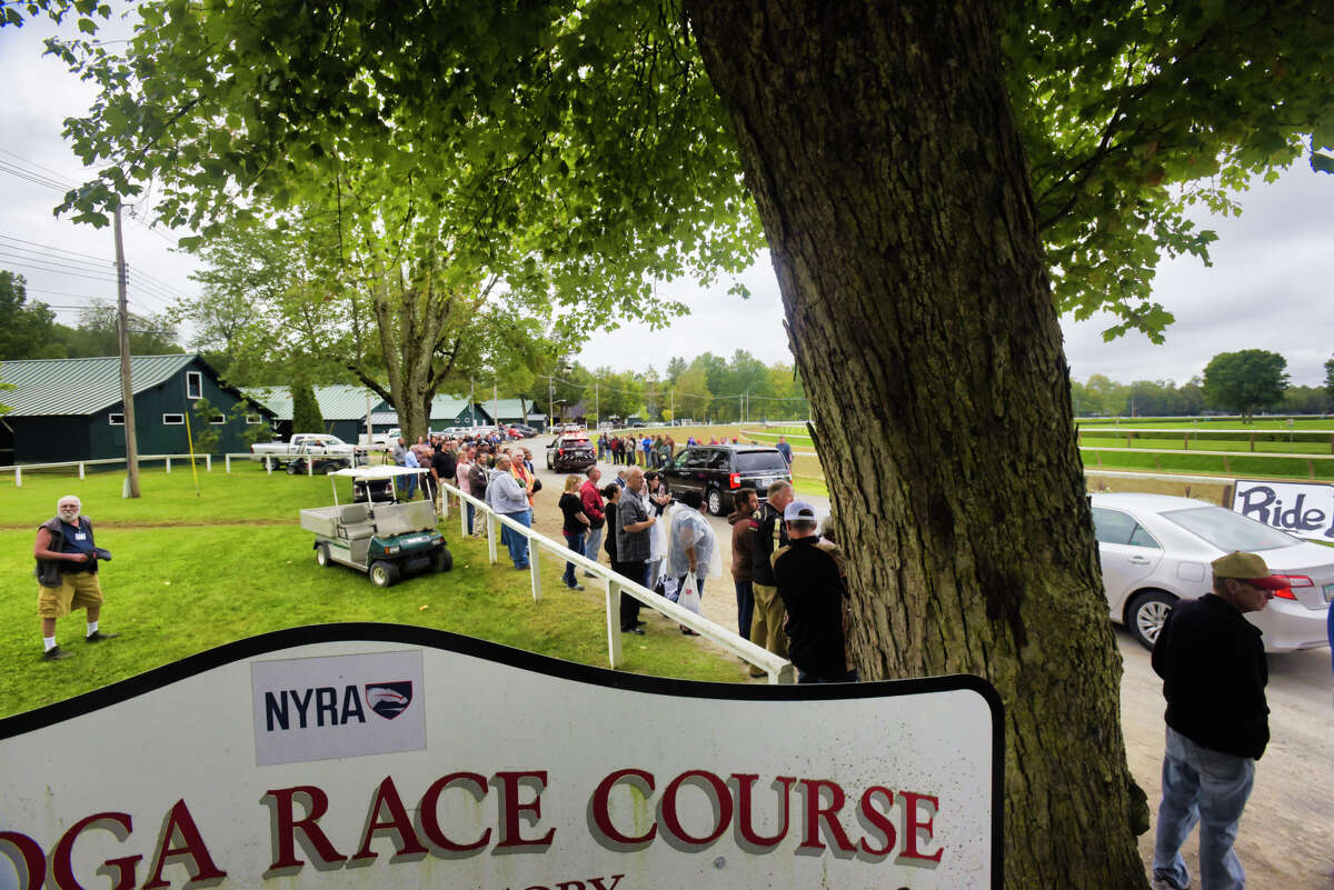 Friends and co-workers of long-time NYRA employee, Frank Fodera Sr., stand along the road through the grounds of the Saratoga Race Course as the funeral procession for Fodera drives by on Thursday, Sept. 12, 2019, in Saratoga Springs, N.Y. Fodera was killed this past Friday while riding his motorcycle. Fodera, who friends say worked for NYRA for 31 years, was most recently the driver of the horse ambulance at the track. On Thursday friends and co-workers lined the road running along side the main track to say their final goodbyes. Friends said that if Fodera was driving a tractor or the water truck around the track as the surface was prepared for the horses he would be the one waving and saying hello to everyone. (Paul Buckowski/Times Union)