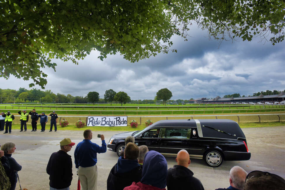 A hearse carrying the body of long-time NYRA employee, Frank Fodera Sr., is driven through the grounds of the Saratoga Race Course on Thursday, Sept. 12, 2019, in Saratoga Springs, N.Y. Fodera was killed this past Friday while riding his motorcycle. Fodera, who friends say worked for NYRA for 31 years, was most recently the driver of the horse ambulance at the track. On Thursday friends and co-workers lined the road running along side the main track to say their final goodbyes. Friends said that if Fodera was driving a tractor or the water truck around the track as the surface was prepared for the horses he would be the one waving and saying hello to everyone. (Paul Buckowski/Times Union)