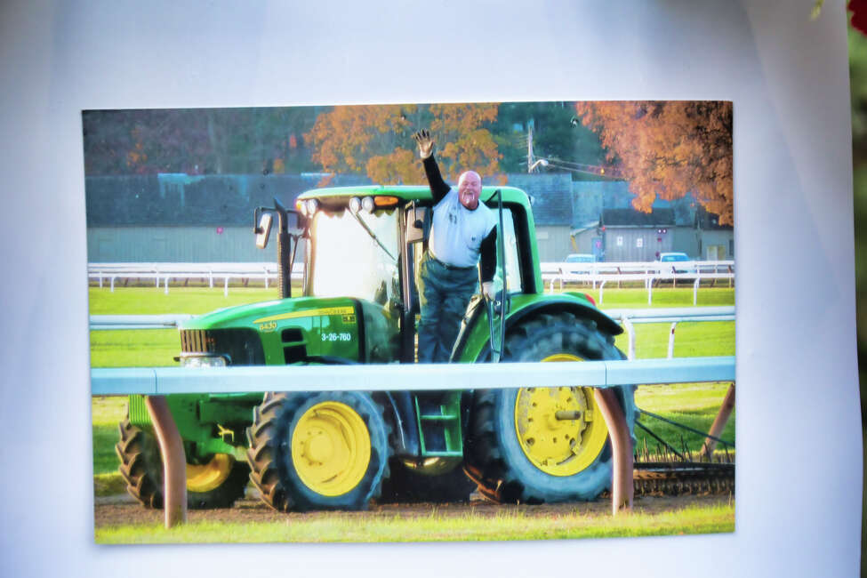 A photo of long-time NYRA employee, Frank Fodera Sr., is seen as part of a memorial as his friends and co-workers gather along the road through the grounds of the Saratoga Race Course as they wait for the funeral procession for Fodera to arrive on Thursday, Sept. 12, 2019, in Saratoga Springs, N.Y. Fodera was killed this past Friday while riding his motorcycle. Fodera, who friends say worked for NYRA for 31 years, was most recently the driver of the horse ambulance at the track. On Thursday friends and co-workers lined the road running along side the main track to say their final goodbyes. Friends said that if Fodera was driving a tractor or the water truck around the track as the surface was prepared for the horses he would be the one waving and saying hello to everyone. (Paul Buckowski/Times Union)