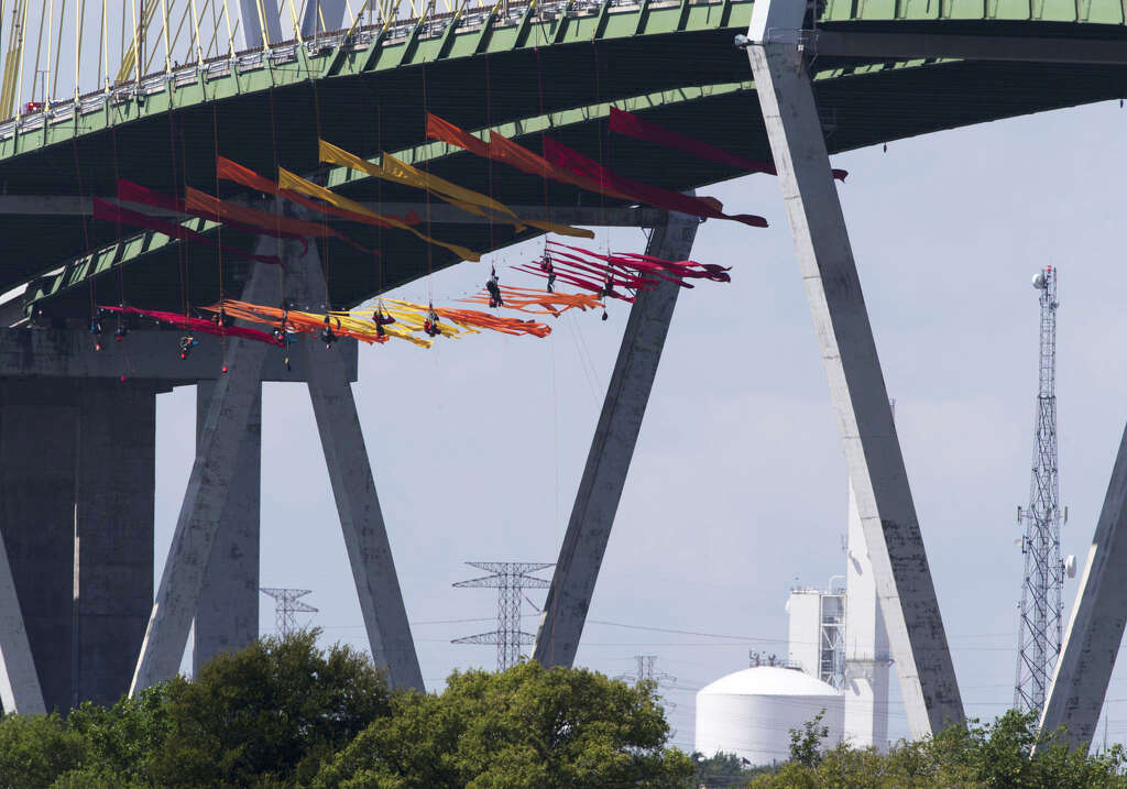 <p>Eleven Greenpeace USA protesters are dangling from the northbound of the Fred Hartman Bridge to protest against the oil industry on Thursday, Sept. 12, 2019, in Baytown. Another 11 spotter for those protesters</p>