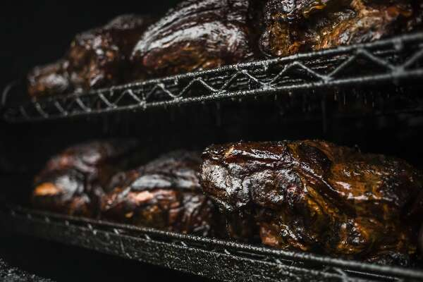 Large pieces of pork cook inside a smoker Tuesday, Sept. 10, 2019 at Bone Daddy's BBQ, located at 1900 S. Saginaw Road, suite F, in the Midland Plaza near China Palace Restaurant and Jimmy John's. The restaurant is set to re-open Tuesday, Sept. 17, 2019. (Katy Kildee/kkildee@mdn.net)