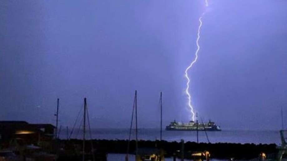 Lightning strikes behind a Washington State Ferry boat as it sailed on the Puget Sound near the Edmonds ferry dock, Sept. 7, 2019. Photo: Randi Lee / KOMO News Photo