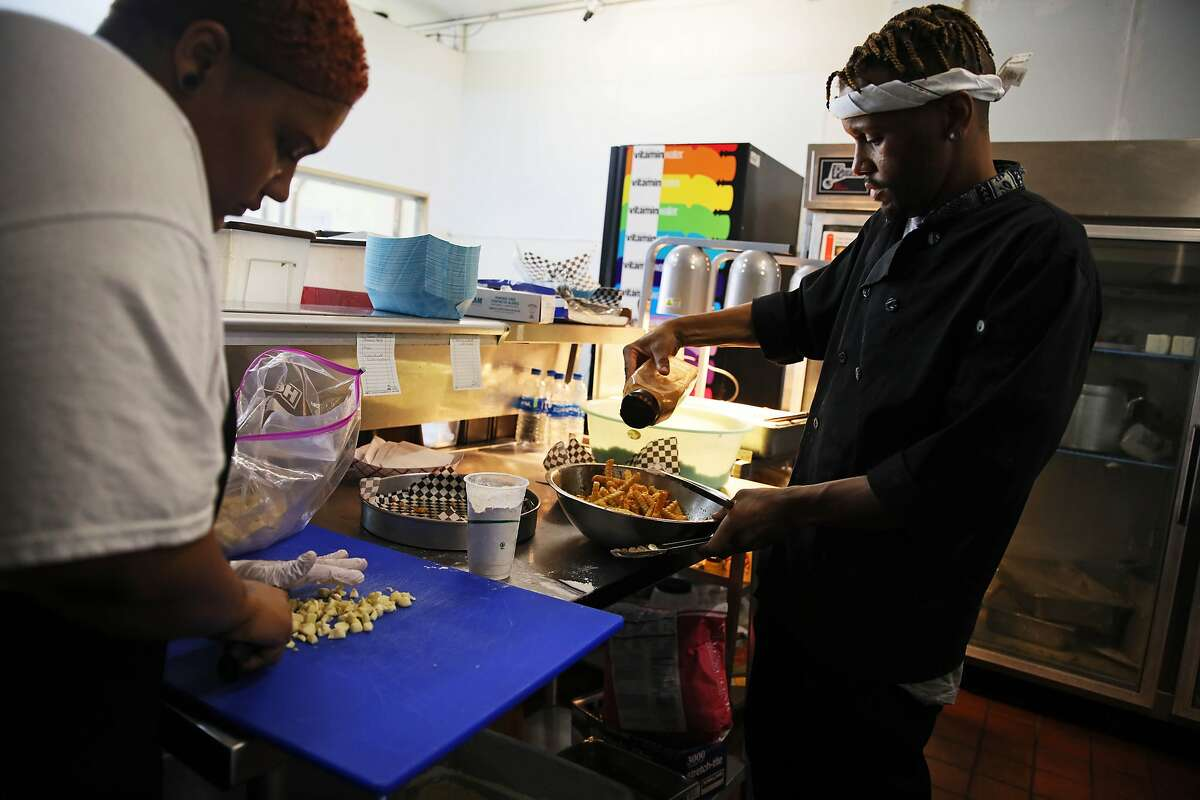 Rianna Armstead, 25, cuts garlic as her brother Rashad Armstead, 31, seasons French fries while they work in the kitchen at Grammie's Down-Home Chicken in Oakland, Calif., on Friday, August 2, 2019.