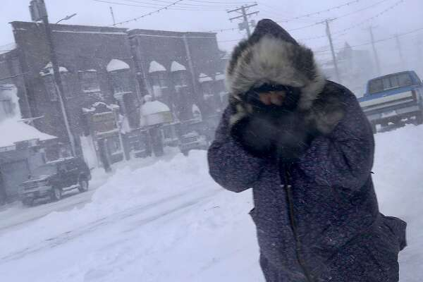 In this Feb. 23, 2019, photo, a woman shields her face from the wind during a snow storm as she walks on Front Street in Nome, Alaska. (AP Photo/Wong Maye-E)