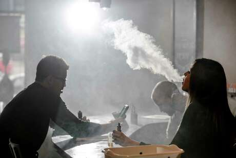 New Element Fine Vapors employee Melissa Torres, right, vapes with Nate Pingor, left, and owner Daniel Adell in the shop Monday, Oct. 26, 2015, in Houston.