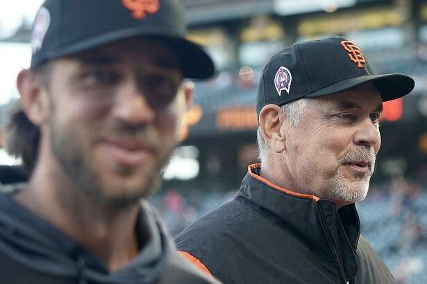 San Francisco Giants manager Bruce Bochy, right, walks back to the dugout with pitcher Madison Bumgarner after the national anthem during a baseball game against the Pittsburgh Pirates Wednesday, Sept. 11, 2019, in San Francisco. (AP Photo/Tony Avelar)