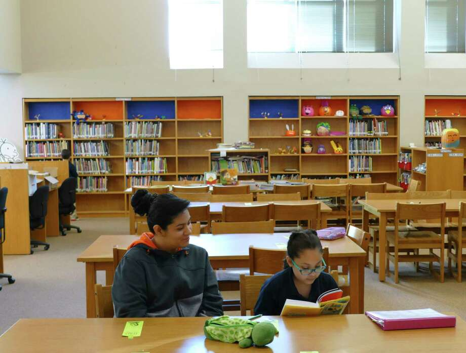 Stefani studies with her mother in the library at Twain Dual Language Academy. The library is filled with books in both languages, part of the principal's mission to make Twain a national model of dual language. Photo: Billy Calzada, Staff Photographer / San Antonio Express-News