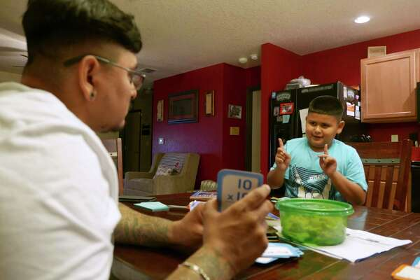 Luis studies math in Spanish with his father, Luis Fabela Sr., last year at their house on the Northeast Side.