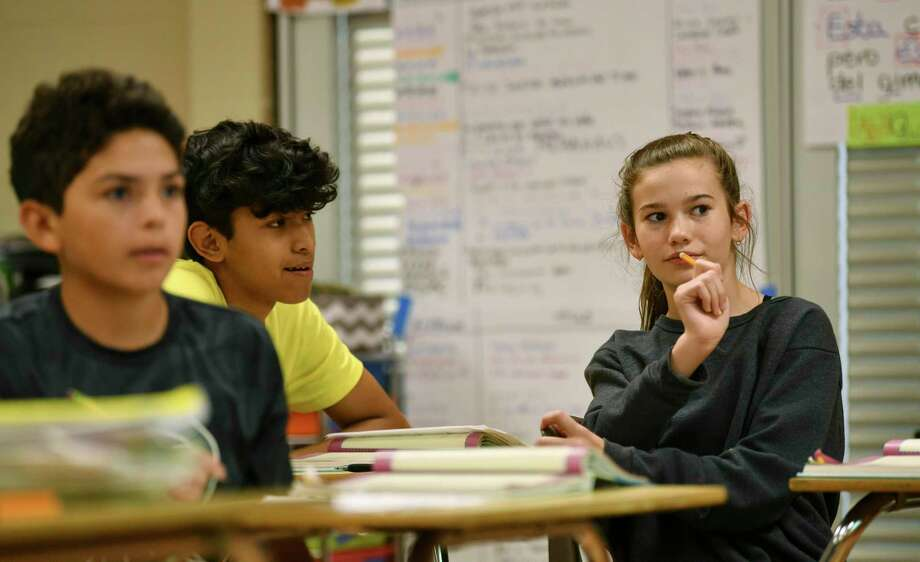 Carli Wilson, right, is a dual language student at Lopez Middle School. She is the only Spanish speaker in her family and often translates emails for her father's work. Photo: Billy Calzada / Billy Calzada