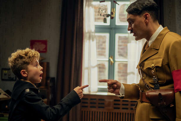 "Roman Griffin Davis, left, and Taika Waititi in ""Jojo Rabbit."""