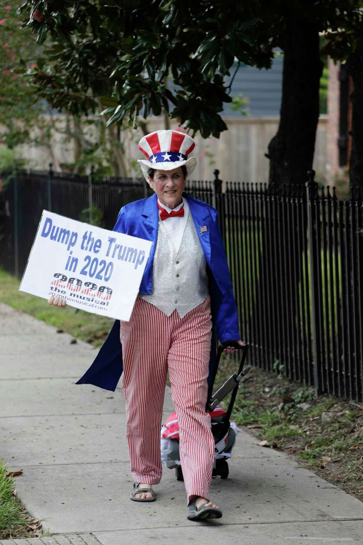 Carol Dunitz walks across the street from the campus of Texas Southern University site of the Democratic presidential primary debates, Thursday, Sept. 12, 2019, in Houston.