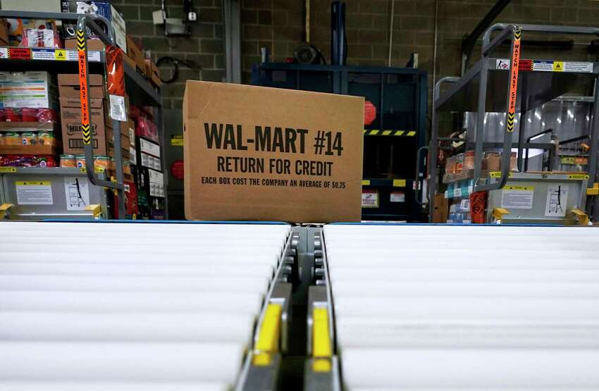 FILE - In this Nov. 9, 2018, file photo, a box of merchandise is unloaded from a truck and sent along a conveyor belt at a Walmart Supercenter in Houston. Walmart is rolling out an unlimited grocery delivery subscription service this fall for a $98 annual fee. The service will reach 1,400 stores in 200 markets and allows the nationa€™s largest grocer to further tap into time-starved shoppers looking for convenience. (AP Photo/David J. Phillip, File)