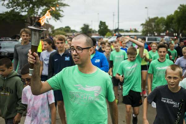 Jameson Baker carries the torch as the Law Enforcement Torch Run kicks off Thursday, Sept. 12, 2019 at the Midland Law Enforcement Center. (Katy Kildee/kkildee@mdn.net)
