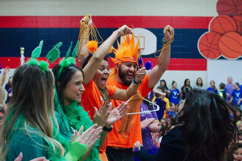 """Deer Park teachers and house leaders, Madison Fattig and Nicole Reyes applaud as  Lisa Palmer and Jake McNeely give a student her orange """"Responsibility House"""" beads during """"Slide Day"""" Thursday, Sep. 12. Photo: Kirk Sides/Staff Photographer"""
