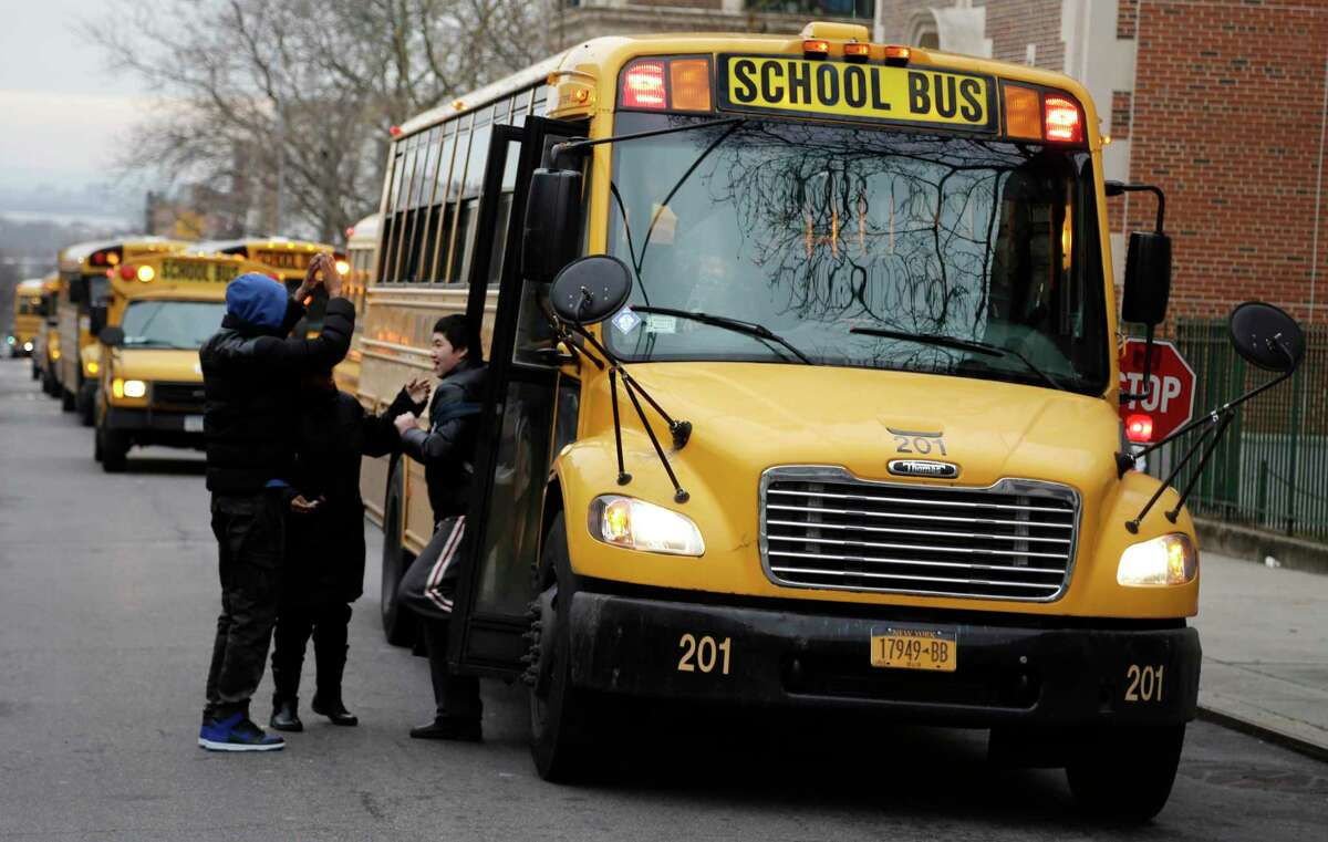 This Jan. 15, 2013 file photo shows school buses lining up to drop off students in New York. New York school districts may now mount speed cameras on the stop arms that extend whenever a bus is stopped under the new law signed Tuesday, Aug. 6, 2019 by Gov. Andrew Cuomo, Drivers caught on camera illegally passing a stopped bus would face fines of $250.(AP Photo/Seth Wenig, File)