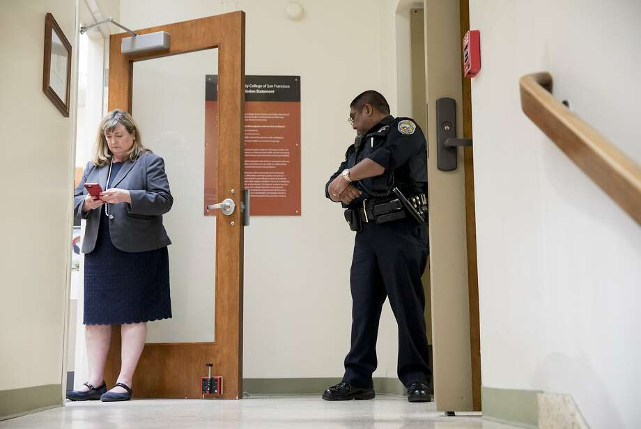 A police officer and aide to Chancellor Mark Rocha stand guard outside of his office as demonstrators inside Conlan Hall protest large executive raises amidst class cuts at City College of San Francisco's Conlan Hall in San Francisco, Calif. Thursday, September 12, 2019. Photo: Jessica Christian / The Chronicle