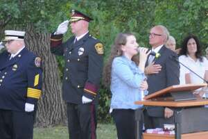 First Selectman Rudy Marconi and members of the Ridgefield Chorale listen as Evelyn Carr sings the national anthem during the annual September 11 memorial ceremony on Danbury Road.