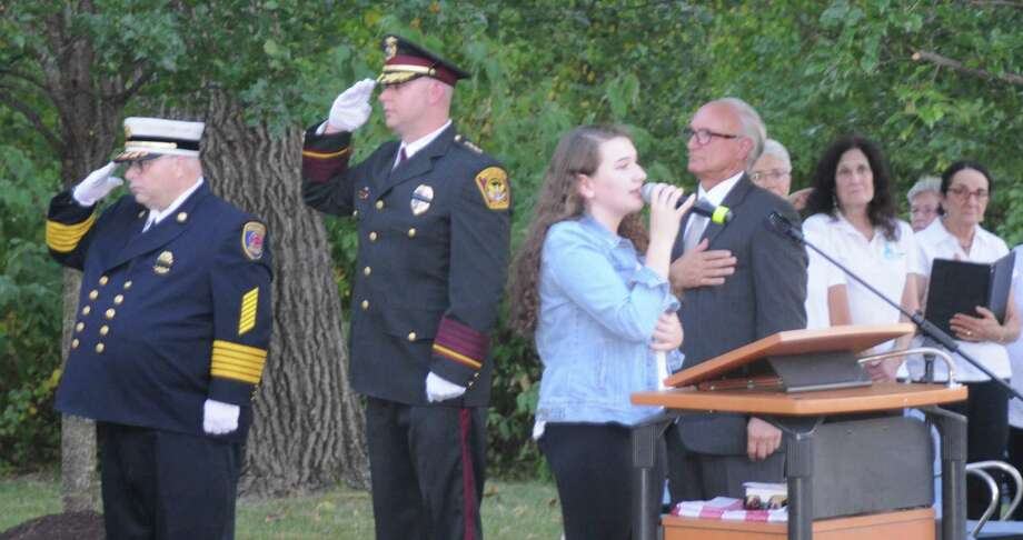 First Selectman Rudy Marconi and members of the Ridgefield Chorale listen as Evelyn Carr sings the national anthem during the annual September 11 memorial ceremony on Danbury Road. Photo: Macklin Reid / Hearst