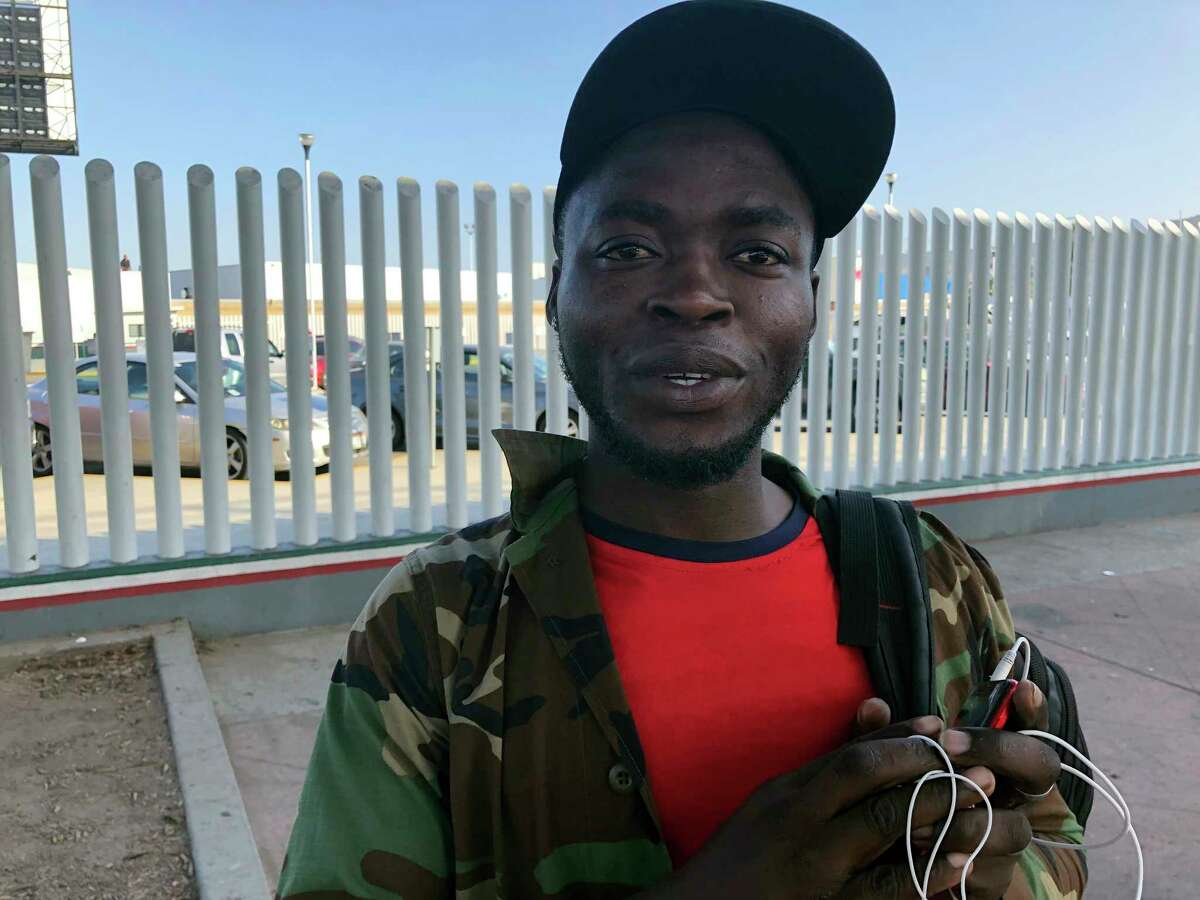 Ngoh Elliot Takere gives an interview in Tijuana, Mexico, where he has been waiting for two months to apply for asylum in the U.S., Thursday, Sept. 12, 2019, on the border with San Diego. Takere left his war-torn Cameroon after being jailed by police for being part of the English speaking minority; paid $400 bail and was released on the condition that he leave the country or the French speaking government would track him down and kill him, he said. (AP Photo/Julie Watson)