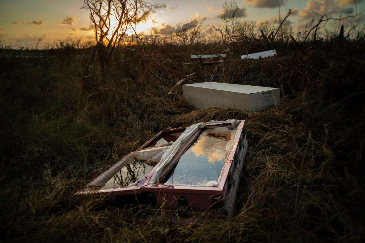 A shattered and water-filled coffin lays exposed to the elements in the aftermath of Hurricane Dorian, at the cemetery in Mclean's Town, Grand Bahama, Bahamas, Wednesday Sept. 11, 2019. Bahamians are tackling a massive clean-up a week after Hurricane Dorian devastated the archipelagoa€™s northern islands. (AP Photo/Ramon Espinosa)
