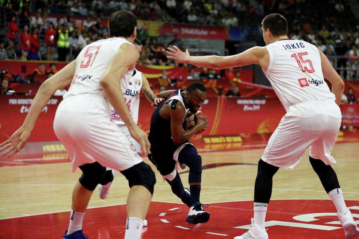 United States' Kemba Walker tries to slip past Serbia's Boban Marjanovic, left and Serbia's Nikola Jokic at right during a consolation playoff game for the FIBA Basketball World Cup in Dongguan in southern China's Guangdong province on Thursday, Sept. 12, 2019. The U.S. will leave the World Cup with its worst finish ever in a major international tournament, assured of finishing no better than seventh after falling to Serbia 94-89 in a consolation playoff game on Thursday night. (AP Photo/Ng Han Guan)
