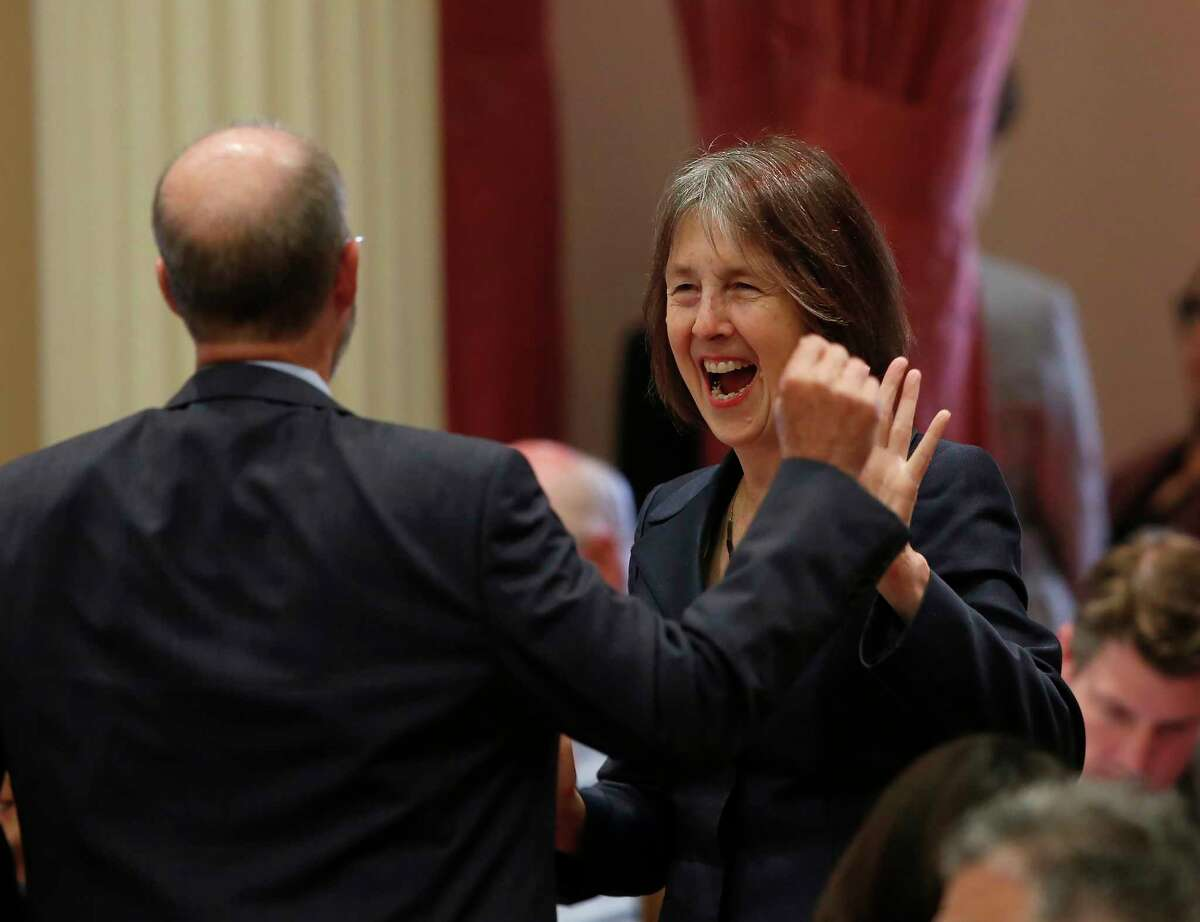 Sen. Nancy Skinner, D-Berkeley, celebrates with Sen. Steven Glazer, D-Orinda, after her measure to let athletes at California colleges hire agents and sign endorsement deals was approved by the Senate in Sacramento, Calif., Wednesday, Sept. 11, 2019. The bill now goes to Gov. Gavin Newsom, who has not said whether he will sign it. But the NCAA Board Of Governors is already urging him not to, sending him a letter Wednesday saying the bill