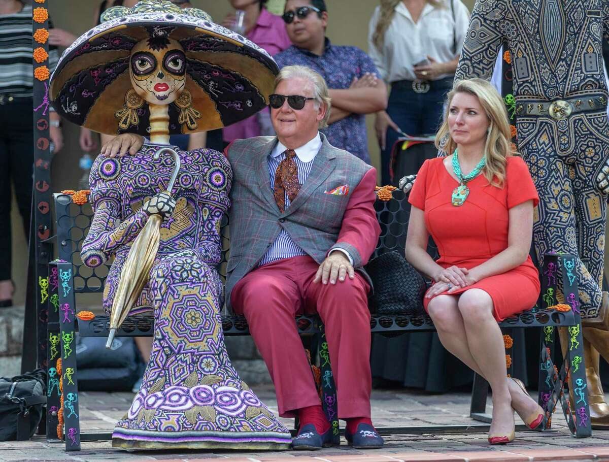 """Robert ?'Dick?"""" Tips, left, jokingly puts his arm around a day of the dead decoration while his wife, Kristin sits next to him Thursday, Sept. 12, 2019 at La Villita during a news conference announcing a new city-sponsored Day of the Dead celebration."""