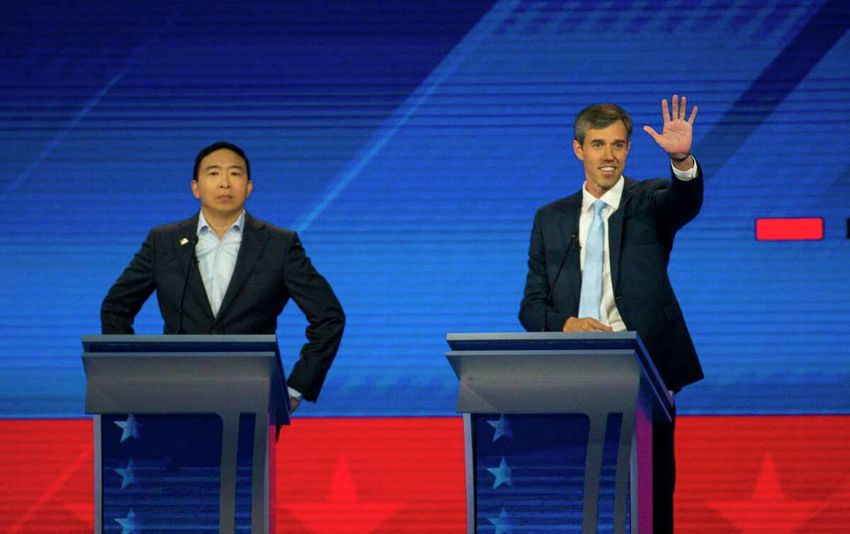 Democratic presidential candidates entrepreneur Andrew Yang and former U.S. Rep. Beto O'Rourke are welcomed to the stage during the Democratic presidential debate inside Texas Southern University's Health & PE Arena in Houston, Thursday, Sept. 12, 2019.