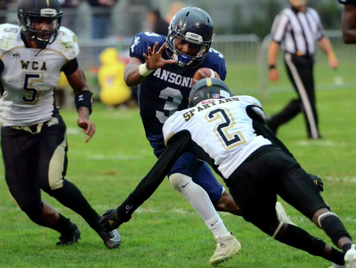 Ansonia's Shykeem Harmon (3) tries to evade WCA's Jone Mwape (2) during high school football action in Ansonia, Conn., on Thursday Sept. 12, 2019.