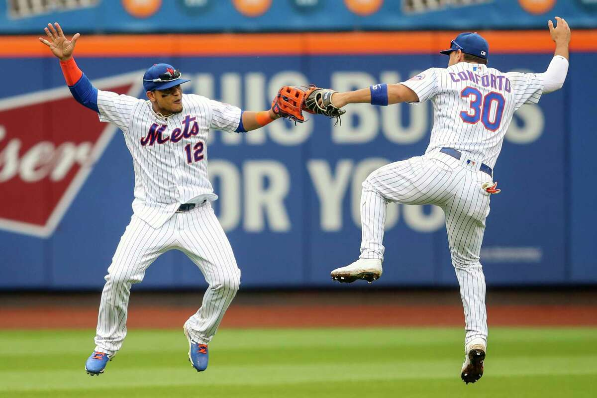 New York Mets' Juan Lagares (12) and Michael Conforto (30) celebrate after defeating the Arizona Diamondbacks during their baseball game, Thursday, Sept. 12, 2019, in New York. (AP Photo/Mary Altaffer)