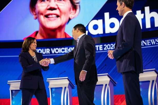 Sen. Kamala Harris (D-Calif.) greets the entrepreneur Andrew Yang at the start of the Democratic Party presidential debate at Texas Southern University in Houston on Thursday, Sept. 12, 2019. At right is former Rep. Beto O'Rourke of Texas. (Tamir Kalifa/The New York Times)