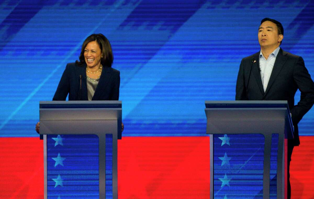 FILE - Democratic presidential candidates Sen. Kamala Harris, D-Calif., and Entrepreneur Andrew Yang listen during the Democratic presidential debate inside Texas Southern University's Health & PE Arena in Houston, Thursday, Sept. 12, 2019.