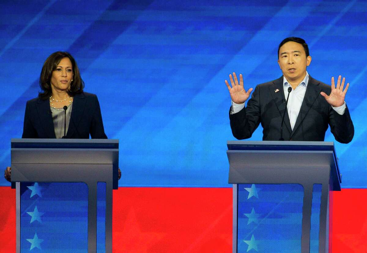 FILE - Democratic presidential candidate entrepreneur Andrew Yang speaks next to Sen. Kamala Harris, D-Calif., during the Democratic presidential debate inside Texas Southern University's Health & PE Arena in Houston, Thursday, Sept. 12, 2019. The latest Emerson poll shows that Yang is leading Harris in her home turf of California.