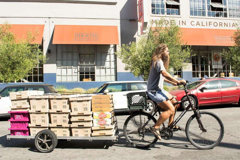 Konstantin Kosov rolls up to his first fruit delivery of the day, Heath Ceramics. Photo: Blair Heagerty / SFGate