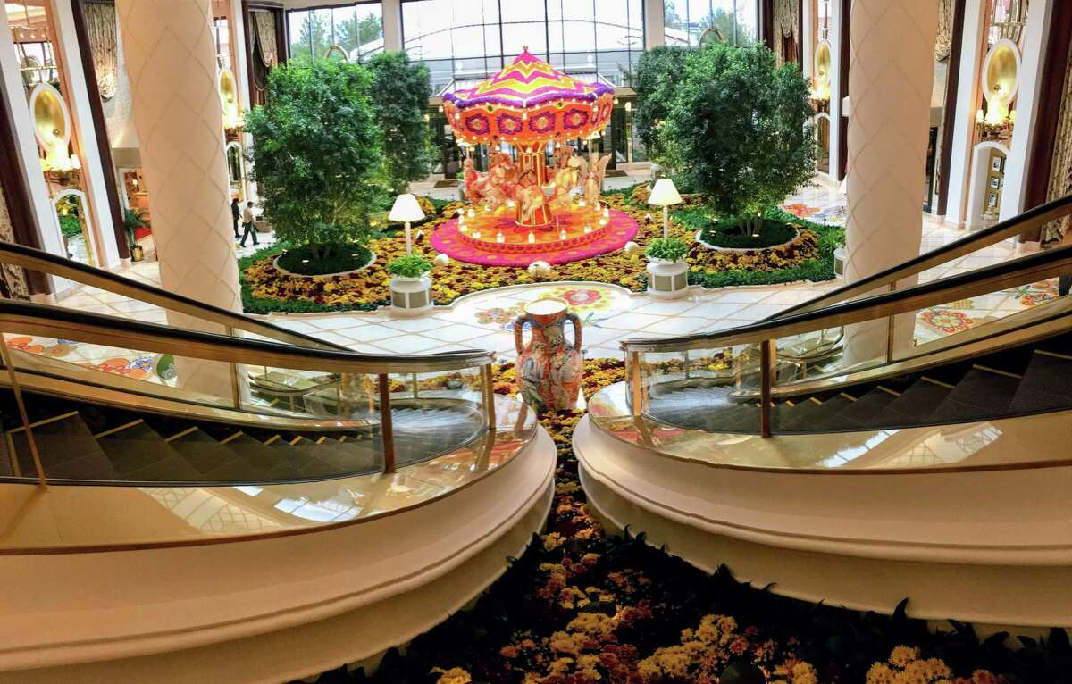 Curved escalators (estimated at more than $5 million alone) lead the eye to the hotel lobby's signature Wynn carousel and live flowers.