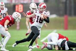 New Canaan's Christian Sweeney (16) evades the grasp of Fairfield Prep's Peter Kavanaugh (27) during the Class LL semifinals last December.