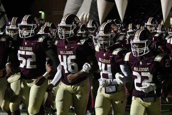 Summer Creek's Caden Wilson (52, Anthony Hall (46), Abel Medina (14), and Torrie Curry (22) lead the Bulldogs on the field before the 2nd half of their matchup with Pasadena Memorial at Turner Stadium in Humble on Sept. 12, 2019.