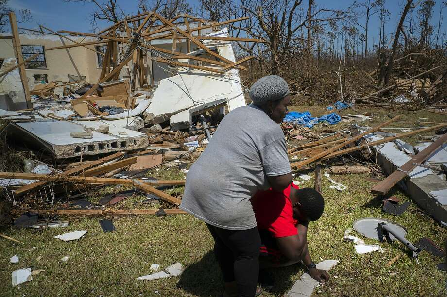 A woman comforts a man who discovered his shattered house and said he had no knowledge of the whereabouts of 8 missing relatives who lived there in High Rock, Grand Bahama. Photo: Ramon Espinosa / Associated Press