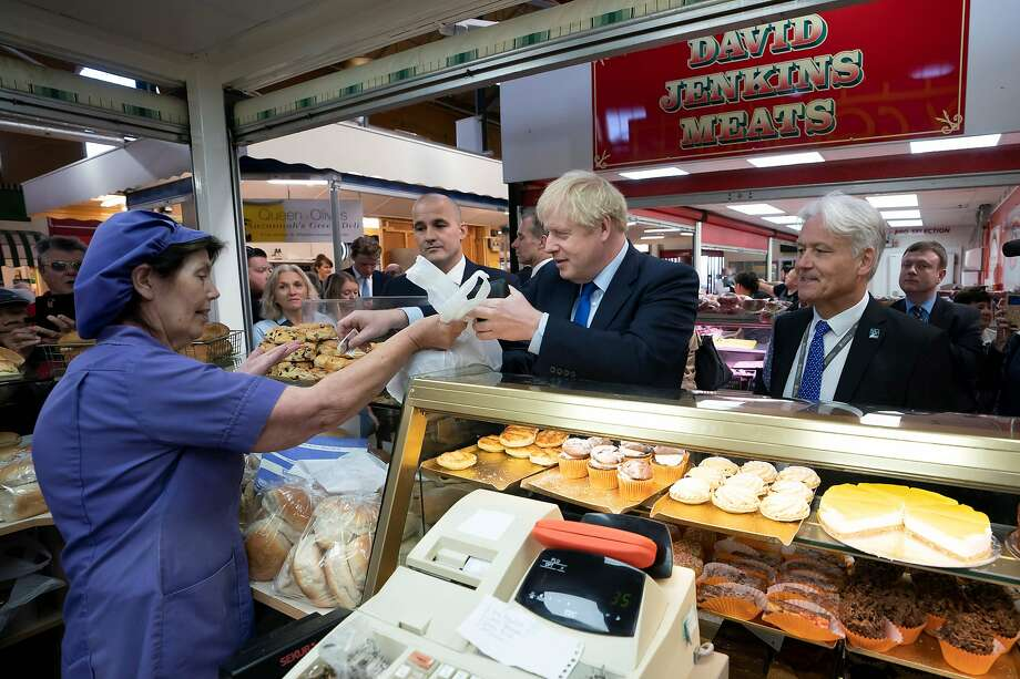 British Prime Minister Boris Johnson pays for food during a visit in the northern town of Doncaster. Photo: Jon Super / AFP / Getty Images