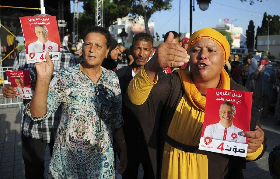 Supporters of jailed presidential candidate Nabil Karoui rally in Tunis. He's charged with money laundering and tax evasion, but allowed to stay in the race. Photo: Hassene Dridi / Associated Press