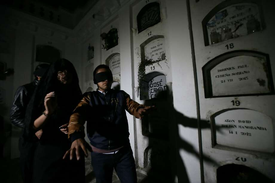 Blindfolded tourists get a taste of death, spending part of the night in a dark crypt at a cemetery in Quito. Latin America has long harbored a mystical fascination with death. Photo: Dolores Ochoa / Associated Press
