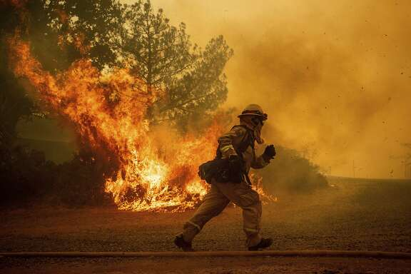 A firefighter running to try and save a home in� Lakeport, Calif. on July 31, 2018. A new report by firefighters takes CalFire to task for its decisions in last year's Mendocino and Lake county fires. (AP Photo/Noah Berger)