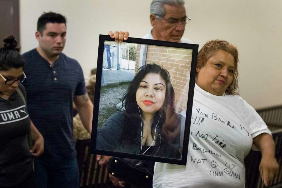 Beatrice Gomez, cousin of victim Cynthia Gomez, displays a picture of her while leaving the courtroom after Christopher Moreno's bond hearing was reset. Photo: Daniel Carde /Special Contributor / Daniel Carde