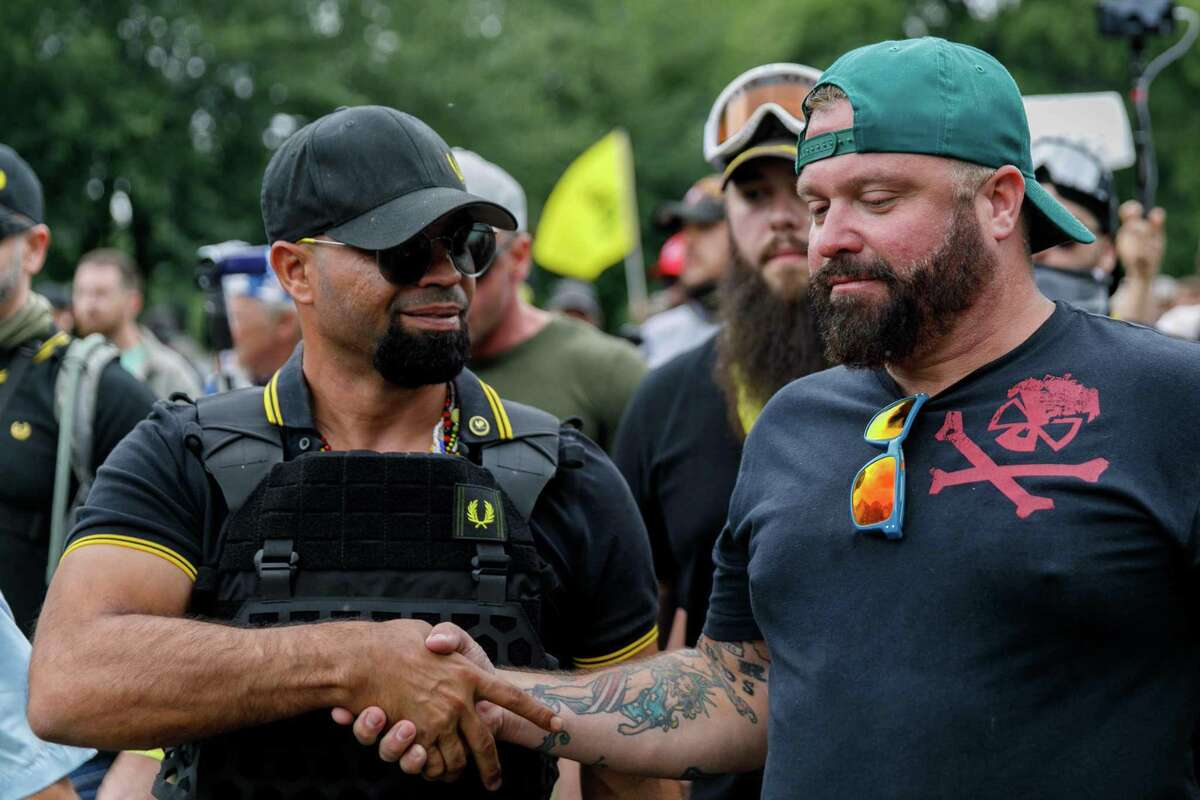 """Leader of the Proud Boys Enrique Tarrio (L) and rally organizer Joe Biggs (R) congratulate each other as they return to the march starting-point over the Hawthorn Bridge as """"The End Domestic Terrorism"""" rally at Tom McCall Waterfront Park concludes on August 17, 2019 in Portland, Oregon. - No major incidents were reported on Saturday afternoon in Portland (western USA) during a far-right rally and far-left counter-demonstration, raising fears of violent clashes between local authorities and US President Donald Trump, who was monitoring the event """"very closely"""". (Photo by John Rudoff / AFP)JOHN RUDOFF/AFP/Getty Images"""